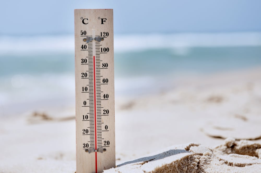 Thermometer sticking out of the sand at beach with high temperatures