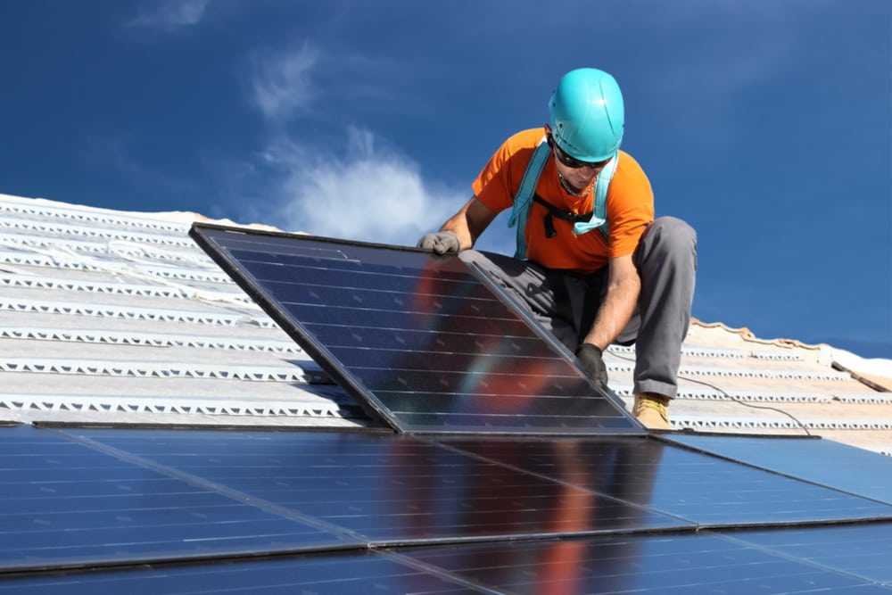 Worker installs solar panels on rooftop